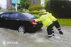 """大雨致道路积水,轿车被困水中无法行驶两名辅警变身""""推车员""""感动路人"""